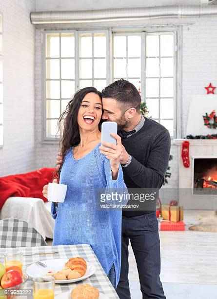 Cheerful couple having breakfast at home and making selfie