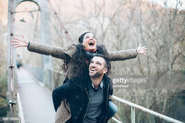 Cheerful couple having fun on a bridge