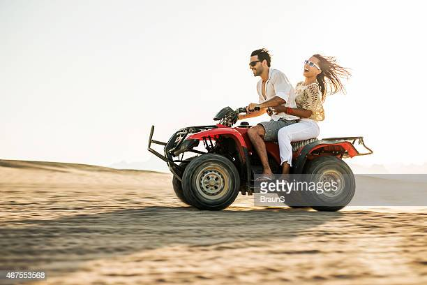 Cheerful couple having fun on a quad bike.