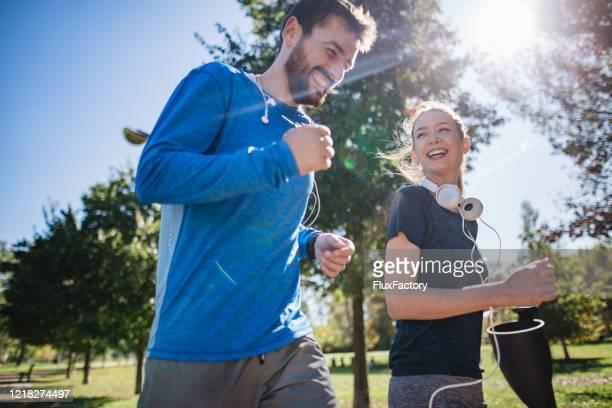 casal alegre se divertindo correndo juntos - sportsperson - fotografias e filmes do acervo