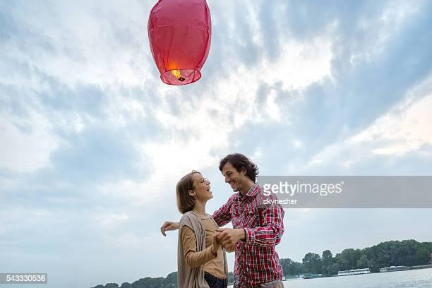 Cheerful couple having fun under Chinese lantern in nature.