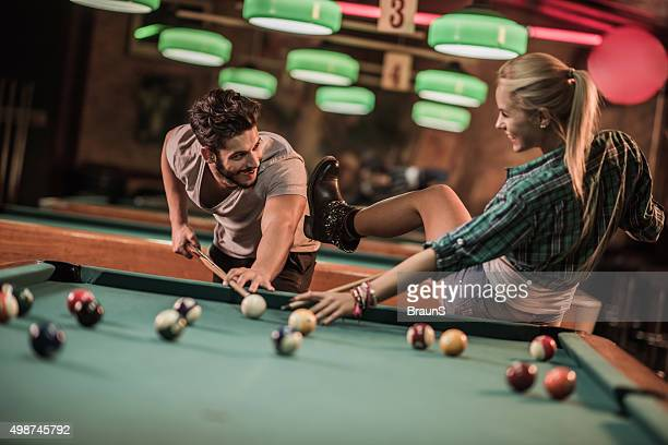 Cheerful couple having fun while playing billiard together.