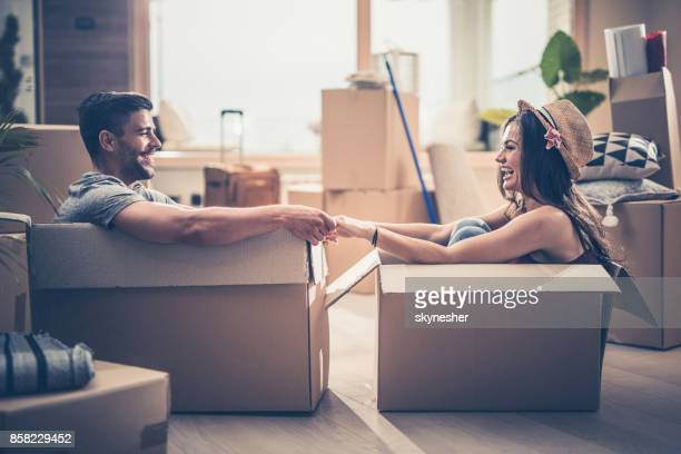 cheerful couple having fun while sitting in cardboard boxes at their new home. - unpacking stock pictures, royalty-free photos & images