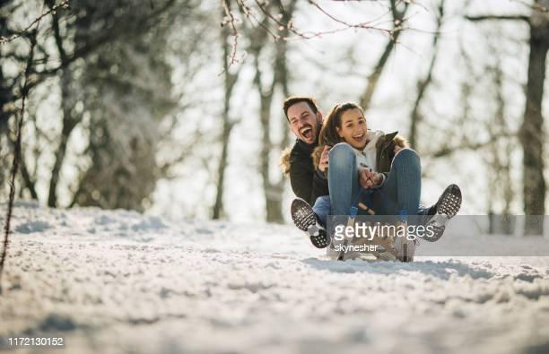 fröhliches paar mit spaß beim schlittenfahren auf einem schnee in der natur. - schlitten stock-fotos und bilder