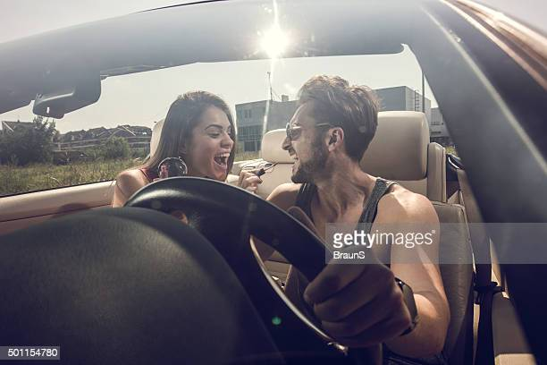 alegre casal se divertindo com make-up de automóvel conversível. - transporte assunto - fotografias e filmes do acervo