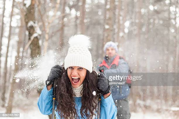 Cheerful couple having fun with snow balls in the forest