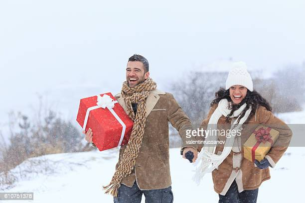 Cheerful couple holding hands and having fun with christmas presents
