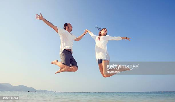Cheerful couple jumping on the beach during summer.