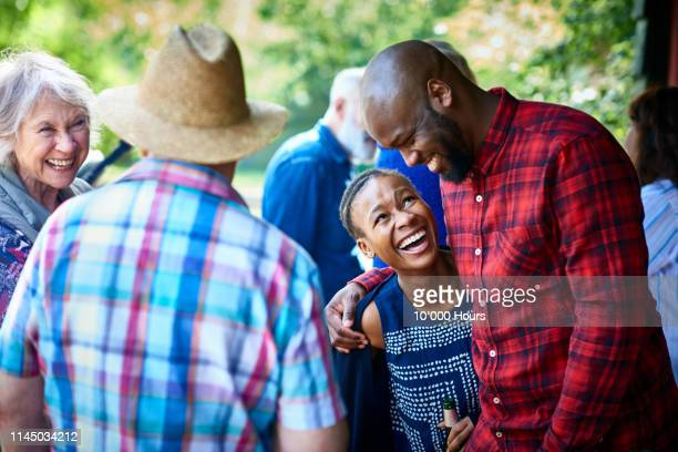 cheerful couple laughing and smiling with friends in garden - incidental people stock pictures, royalty-free photos & images