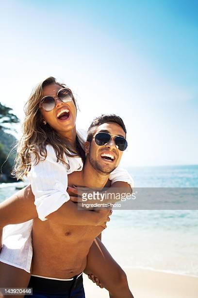 Alegre casal, Homem Cavalitas Uma Mulher bonita na praia.