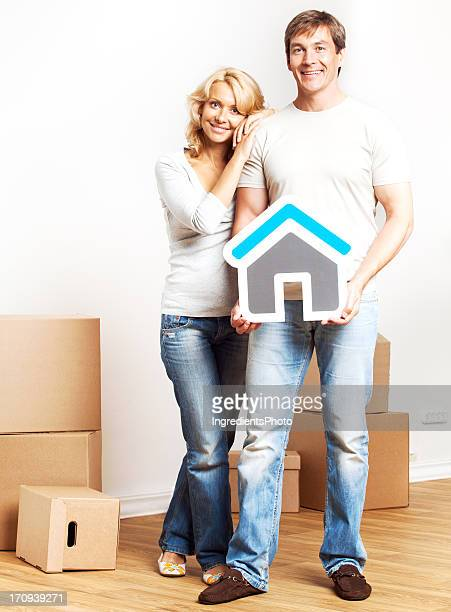 Cheerful couple moving into new home and holding house sign.