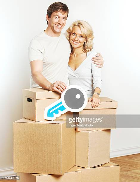 Cheerful couple moving into new home and holding key sign.