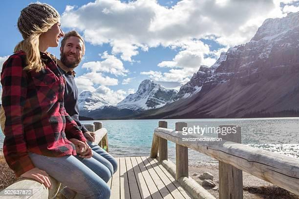Cheerful couple on log bridge admiring landscape