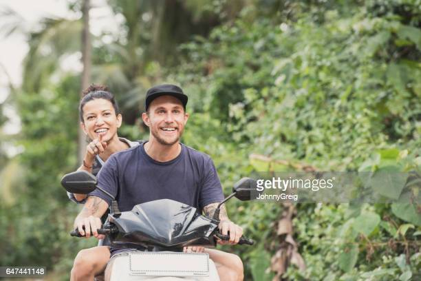 cheerful couple on moped with woman pointing - moped stock photos and pictures
