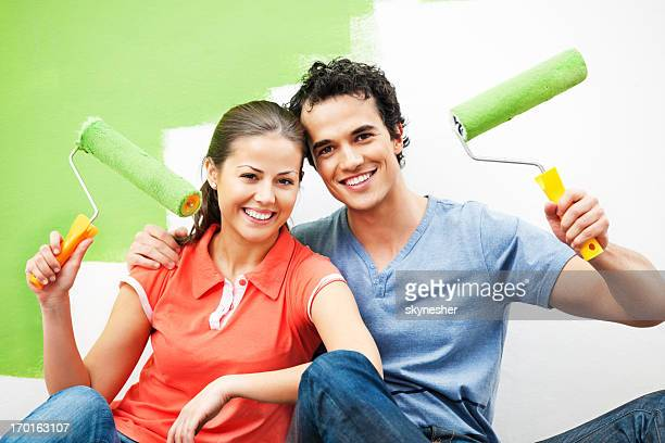 Cheerful couple painting the wall