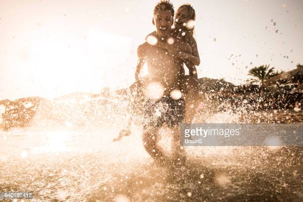 Cheerful couple piggybacking in the sea at sunset.