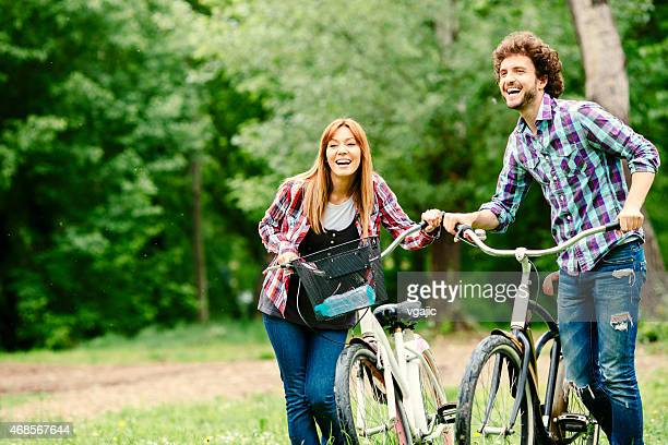 Cheerful couple pushing bicycles and walking.