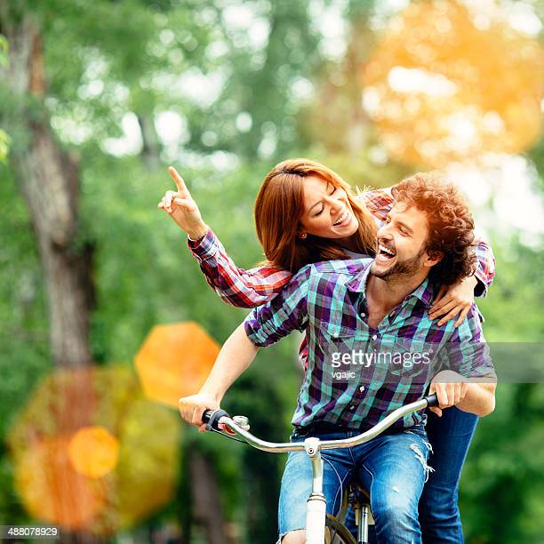 Cheerful Couple Riding Bicycle Together.