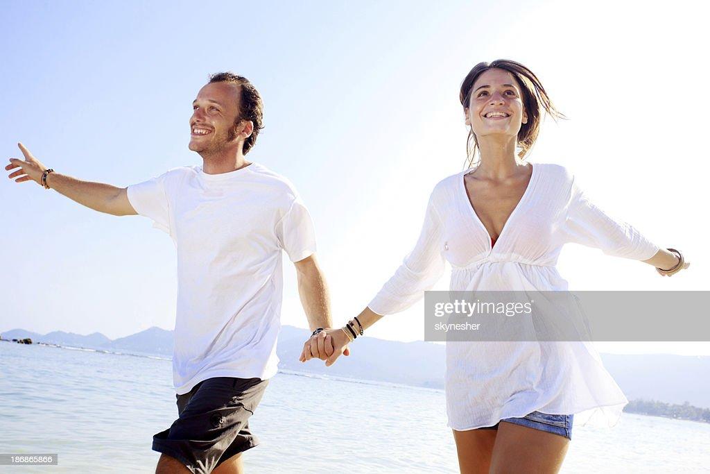 Cheerful couple running on the beach. : Stock Photo