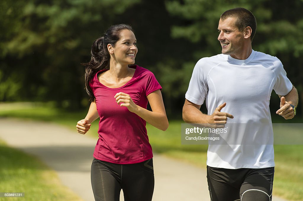 Cheerful couple running outdoors
