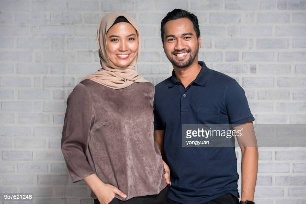 cheerful couple smiling and looking at camera - muslim couple stock pictures, royalty-free photos & images