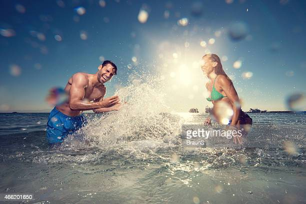 Cheerful couple splashing each other in the sea.