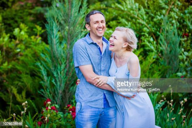 Cheerful Couple Standing Against Plants At Park