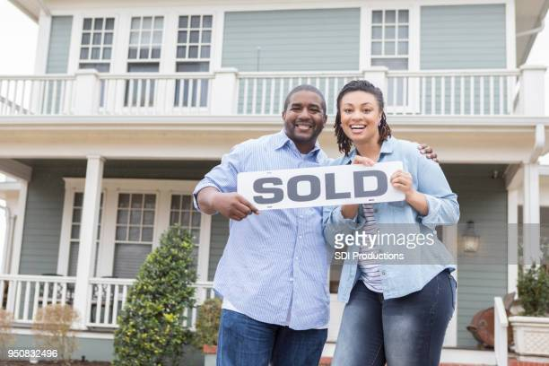 Cheerful couple standing in front of their new home