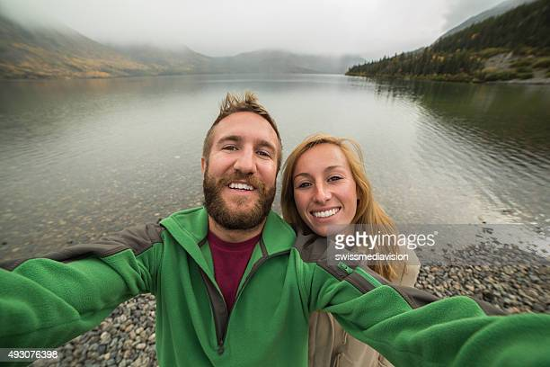 Cheerful couple takes selfie portrait near lake on foggy day