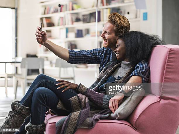 Cheerful couple taking a selfie with mobile phone.