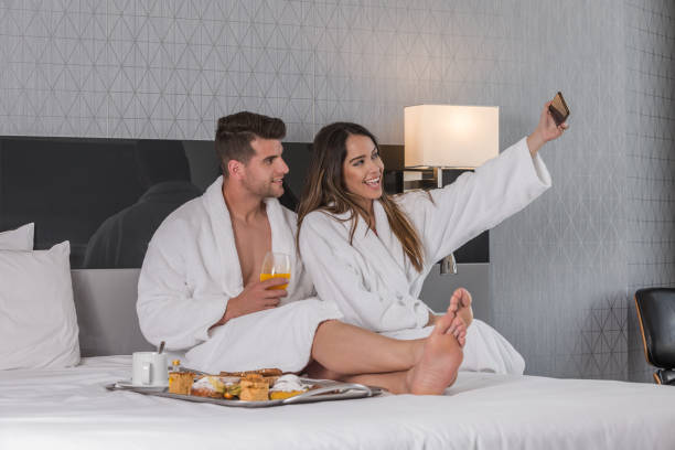 Cheerful couple taking selfie during breakfast in hotel bedroom
