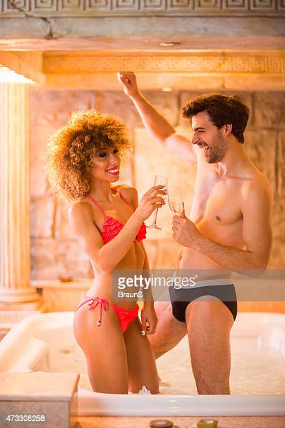 Cheerful couple toasting in hot tub and having fun.