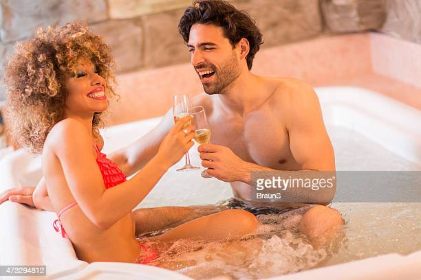 Cheerful couple toasting with champagne in a hot tub.