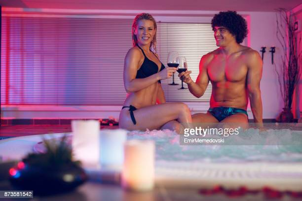 Cheerful couple toasting with red wine in a hot tub.