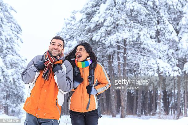 Cheerful couple tourists hiking in snow forest
