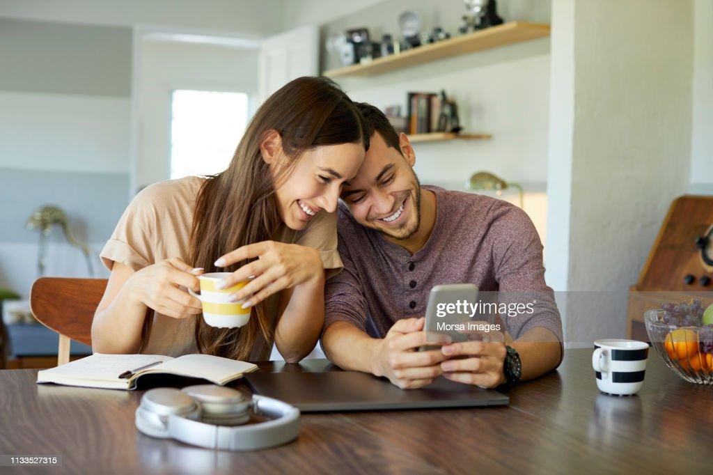 Pares alegres usando o telefone móvel na sala de jantar : Foto de stock