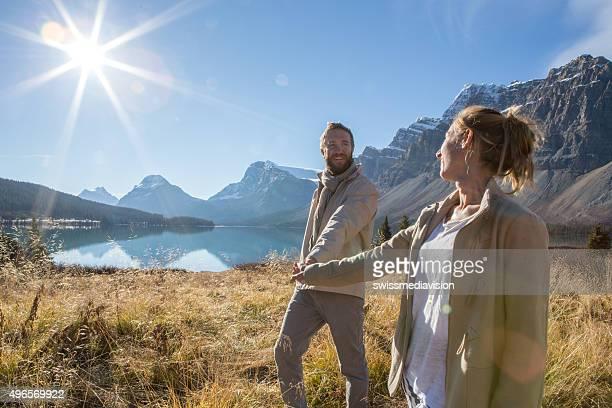 Joyeux couple marchant dans la Prairie tenant les mains