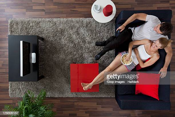A cheerful couple watching TV and eating popcorn in their living room, overhead view