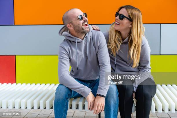 cheerful couple wearing sunglasses sitting on seat against colorful wall - girlfriend stock pictures, royalty-free photos & images