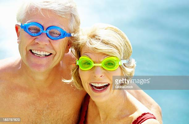 cheerful couple wearing swimming goggles - swimming goggles stock pictures, royalty-free photos & images