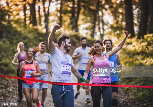 cheerful couple winning marathon race in the forest and crossing finish line together. - finishing line stock pictures, royalty-free photos & images