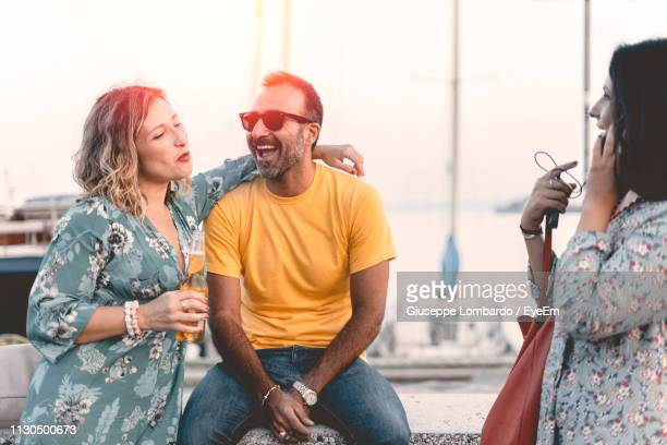 cheerful couple with female friend at harbor - yellow dress stock pictures, royalty-free photos & images