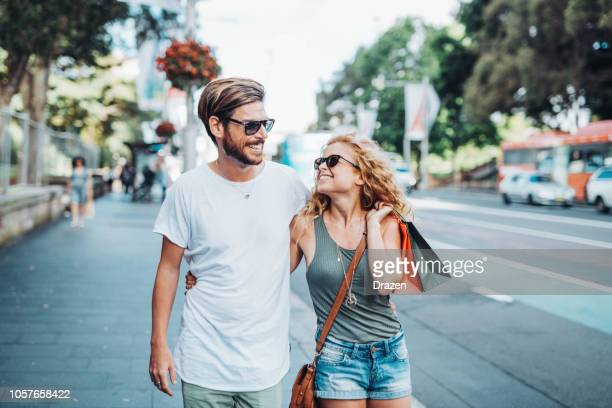 cheerful couple with shopping bags and christmas gifts in summer time - financial district stock pictures, royalty-free photos & images