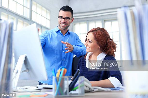 Cheerful coworkers working on computer in the office