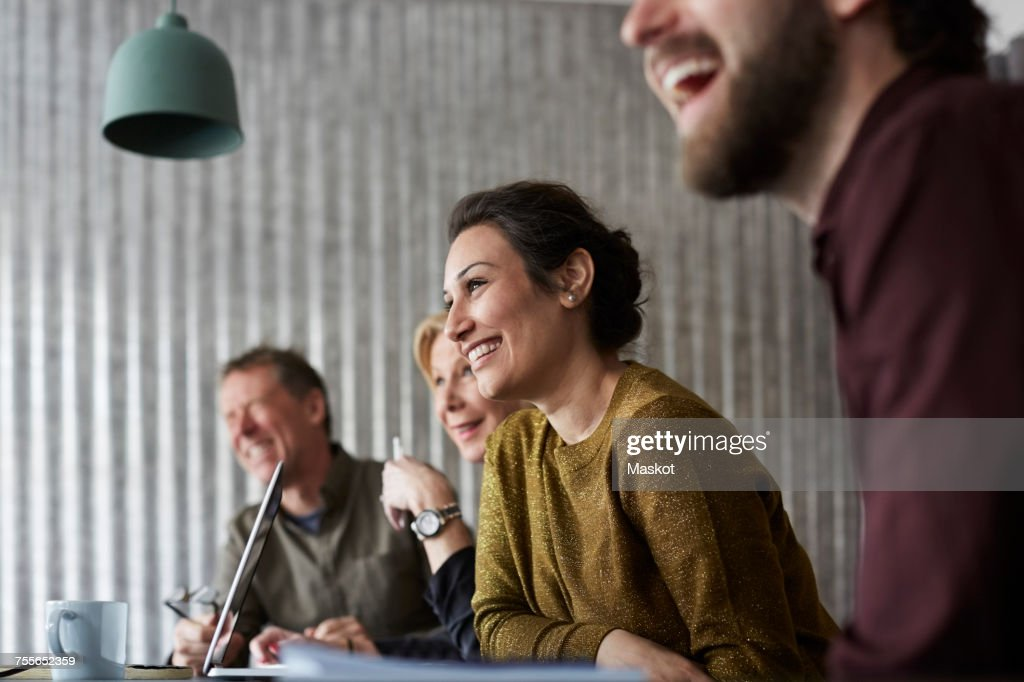 Cheerful creative business colleagues sitting at conference table while looking away in board room : Stock Photo