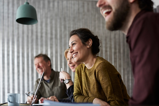 Cheerful creative business colleagues sitting at conference table while looking away in board room - gettyimageskorea