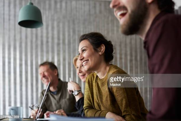 cheerful creative business colleagues sitting at conference table while looking away in board room - società foto e immagini stock
