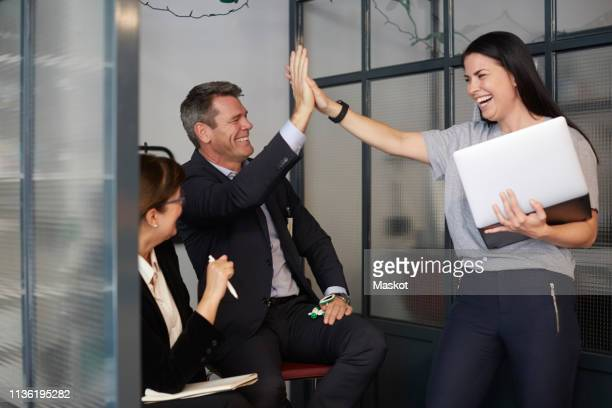 cheerful creative businesswoman high-fiving with male bank manager during meeting in office - cheerful stock pictures, royalty-free photos & images
