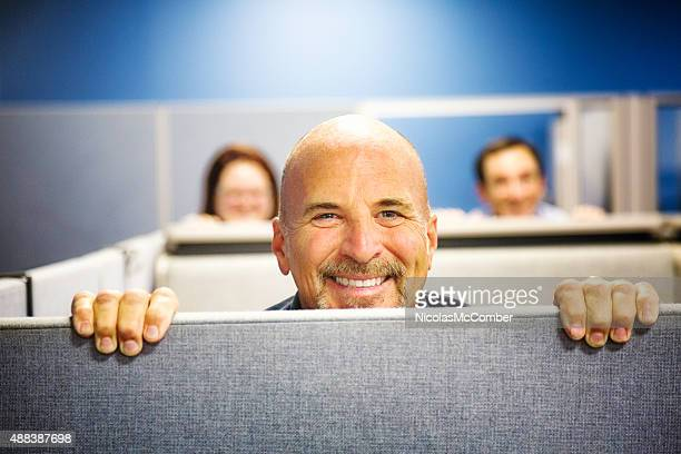 Cheerful cubicle worker portrait peeking over wall smiling