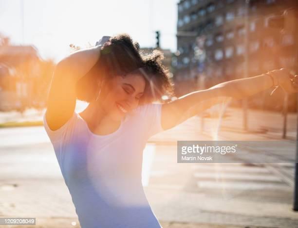 cheerful curly hair woman dancing on street - womens day stock-fotos und bilder
